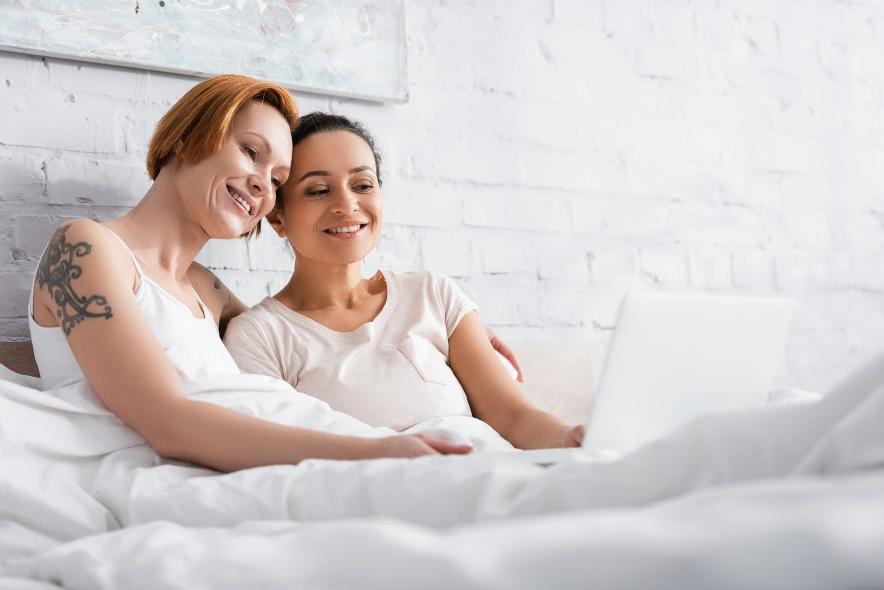 women watching porn on a laptop together in bed